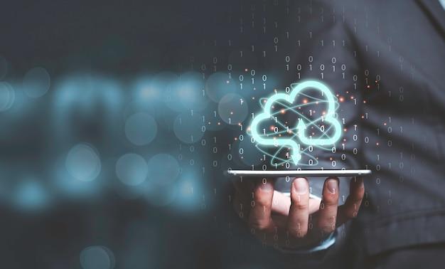 データ情報を転送し、ダウンロードアプリケーションをアップロードするために携帯電話で仮想クラウドコンピューティングを保持しているビジネスマン。技術変革のコンセプト。