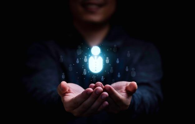 焦点の顧客グループまたは人間の募集と開発の概念のための仮想人間のアイコンを保持しているビジネスマン。