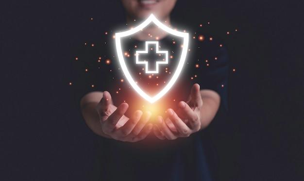 Бизнесмен, держащий виртуальный защитный знак здоровья и страхования с копией пространства.