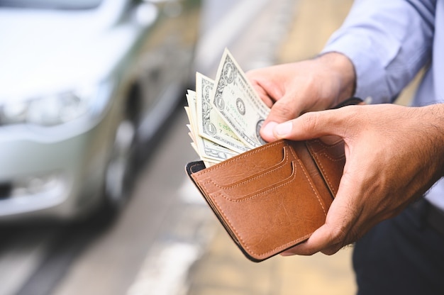 Businessman holding a wallet in the hands and take money out of pocket on car wall