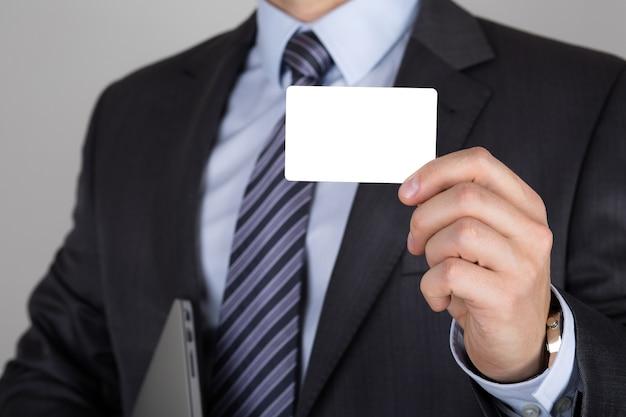 白い名刺を持っているビジネスマン。ビジネス会議またはプレゼンテーションの概念