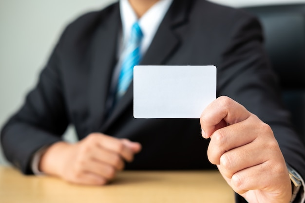 Businessman holding a white business card on table at office room.