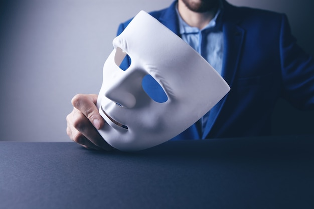 Businessman holding white mask in his hand