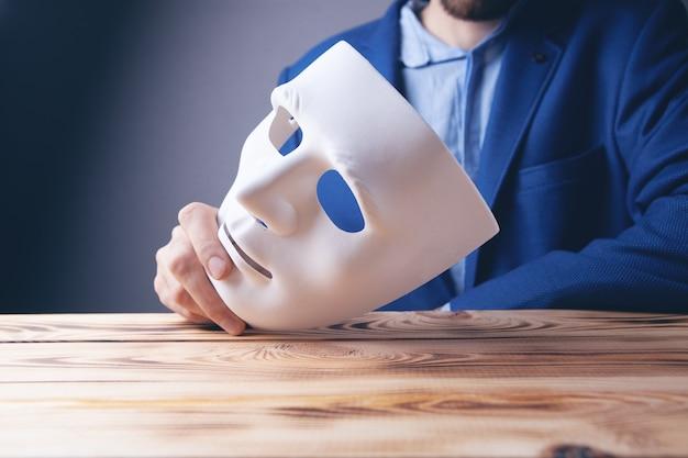 手に白いマスクを保持しているビジネスマン