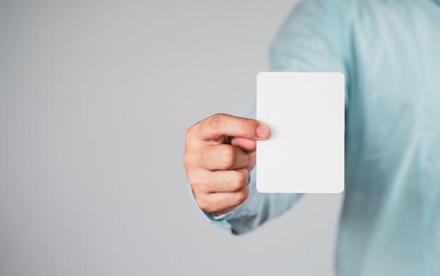 ホワイトペーパー、メモまたはカードを保持しているビジネスマン