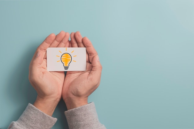 Businessman holding white paper with lightbulb glowing drawing on hand for creative thinking idea and innovative technology concept.