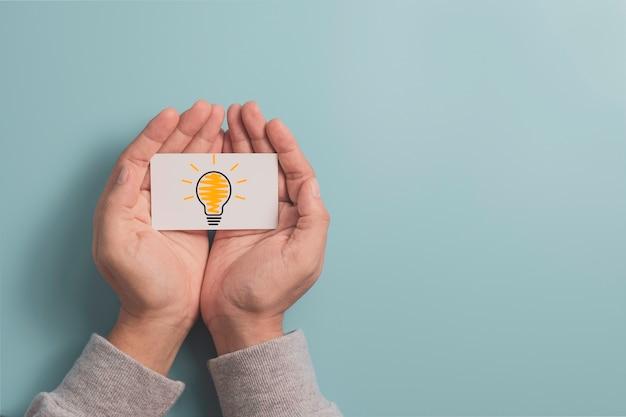 創造的な思考のアイデアと革新的な技術の概念のために手元に電球の光る図面と白い紙を持っているビジネスマン。
