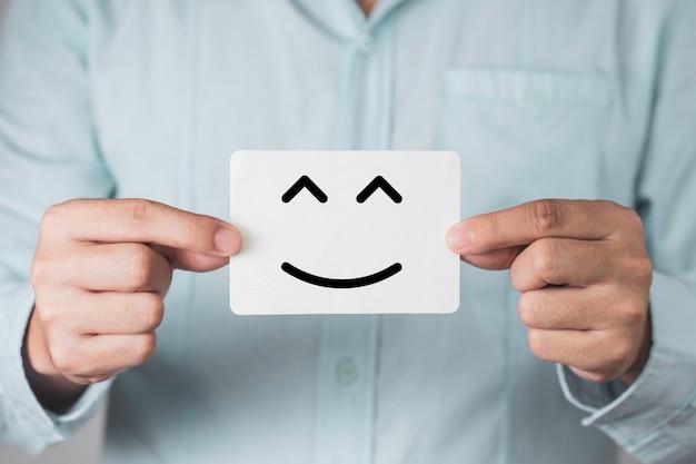白い紙を持って、笑顔や幸せの顔を示すビジネスマン。