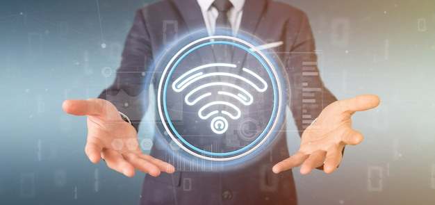 Businessman holding wifi icon with stats and binary code