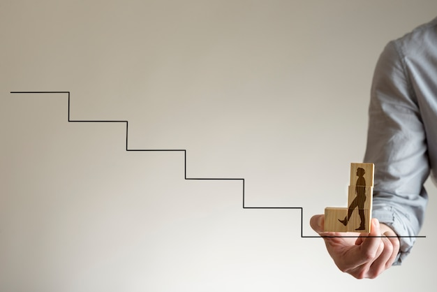 Businessman holding with his fingers wooden blocks with shape of man walking up stairs to climb up career ladder.