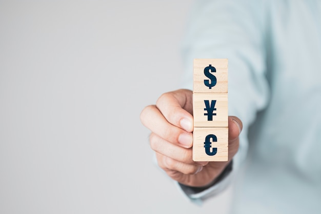 Businessman holding wooden cubes block which print screen dollar yuan and euro sign with copy space. currency exchange concept.