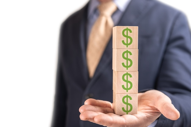 Бизнесмен, держащий деревянные кубики со знаком доллара