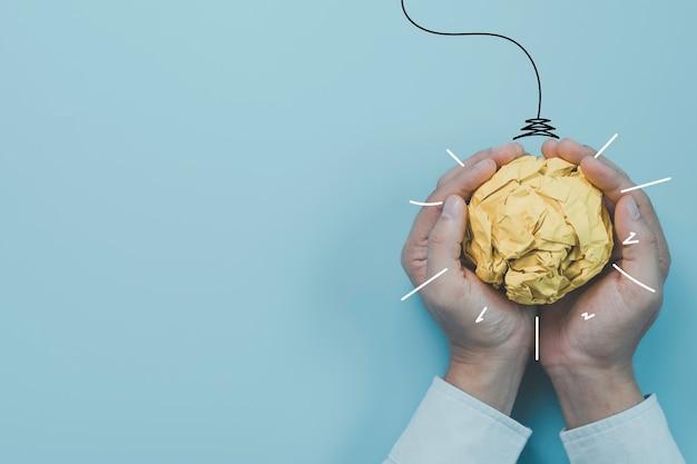 仮想電球のイラストの絵と黄色のスクラップ紙のボールを保持しているビジネスマン。それは創造的思考のアイデアとイノベーションのコンセプトです。