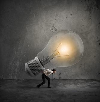 사업가 큰 전구를 보유하고있다. 개념을 실현할 좋은 아이디어를 가지고
