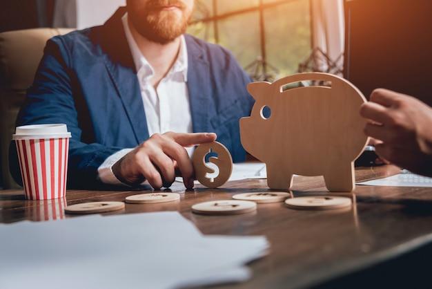 ビジネスマンは木製の貯金箱の近くのコインを保持しています。貯金箱。稼ぐ銀行でお金を集めます。