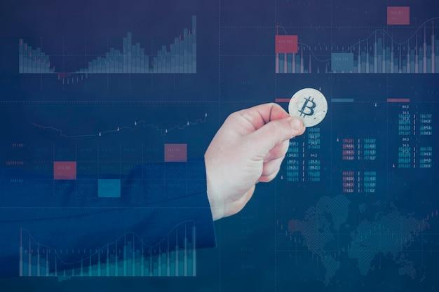 Бизнесмен держит в руках золотую монету bitcoin. информационная голографическая панель со статистикой показывает падение и рост криптовалюты. виртуальная валюта и концепция блокчейна.