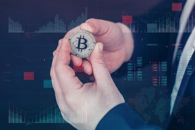 사업가는 금 비트코인 동전을 손에 들고 있습니다. 통계가 있는 정보 홀로그램 패널은 암호화폐의 하락과 성장을 보여줍니다. 가상 통화 및 블록체인 개념입니다.