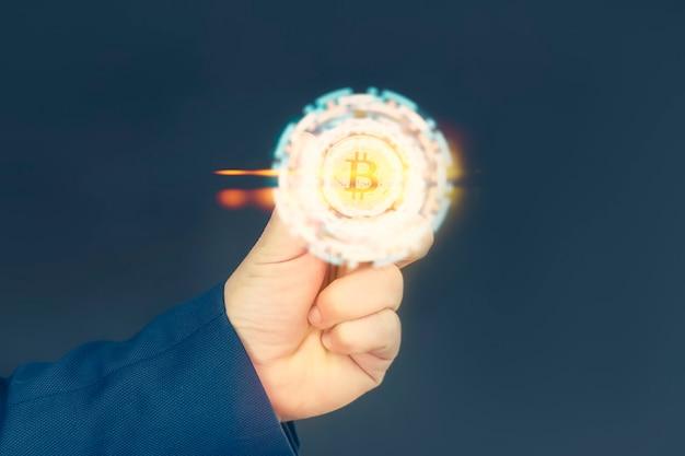 ビジネスマンは彼の手に金のビットコインコインを持っています。明るい光の効果を持つ情報ホログラフィックパネル。仮想通貨とブロックチェーンの概念。