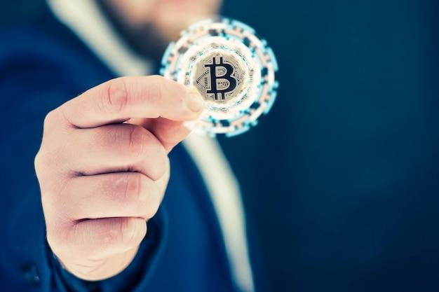 사업가는 금 비트코인 동전을 손에 들고 있습니다. 밝은 조명 효과가 있는 정보용 홀로그램 패널. 가상 통화 및 블록체인 개념입니다.