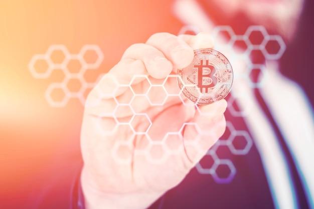 사업가는 금 비트코인 동전을 손에 들고 있습니다. 밝은 조명 효과가 있는 정보용 홀로그램 패널. 가상 통화 및 블록체인 개념입니다. 프리미엄 사진