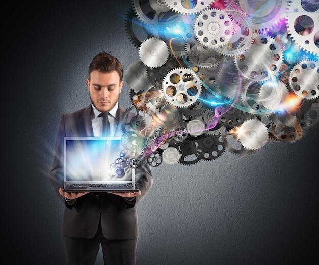 사업가 화면에서 나오는 기어 메커니즘이있는 노트북을 보유하고 있습니다.