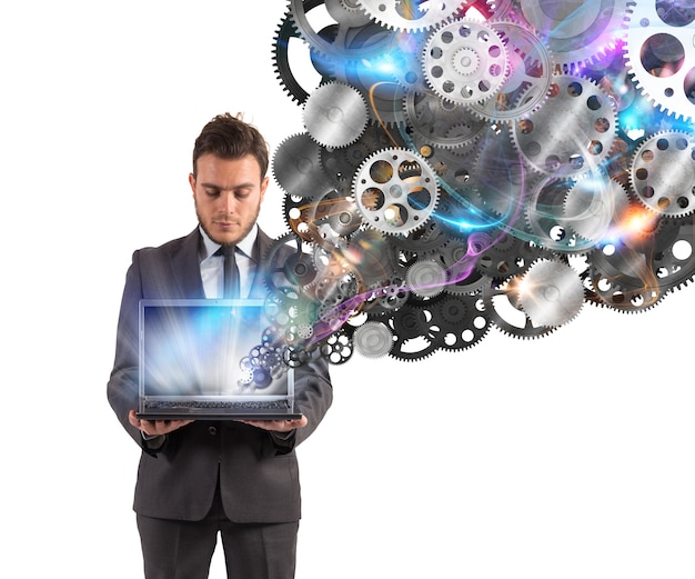 Бизнесмен держит ноутбук с шестеренчатым механизмом, выходящим из экрана