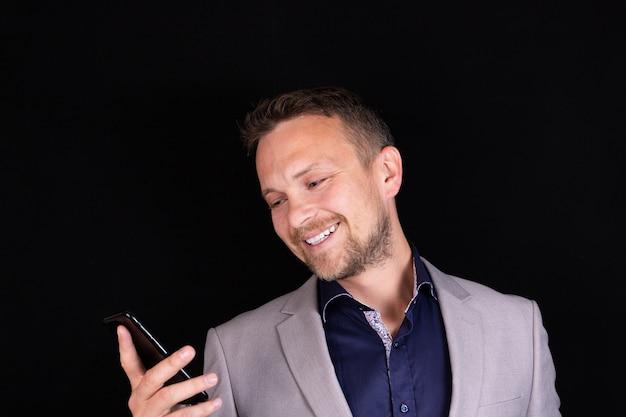 ビジネスマンは携帯電話を手に持って、会話から感情を表現します