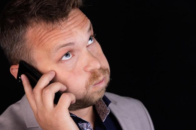 ビジネスマンは彼の手で携帯電話を持って、感情を表現します