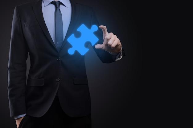 ビジネスマンは彼の手でパズルジグソーパズルのピースを持っています。ビジネスにおける協力、チームワーク、ヘルプとサポートの概念。