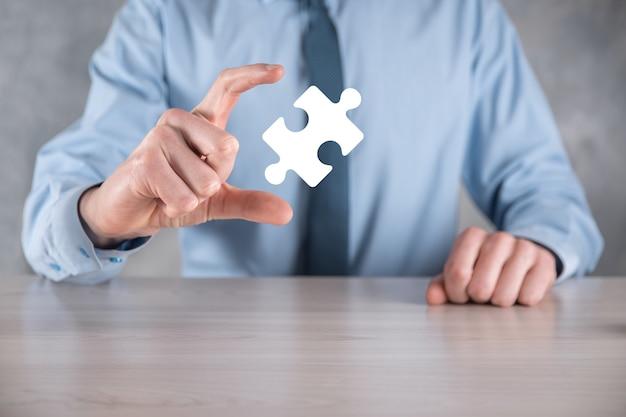 사업가 그의 손에 퍼즐 퍼즐 조각을 보유하고 있습니다. 협력, 팀워크, 도움 및 비즈니스 지원의 개념.
