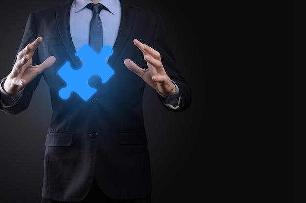 Бизнесмен держит в руках кусок головоломки. концепция сотрудничества, совместной работы, помощи и поддержки в бизнесе.