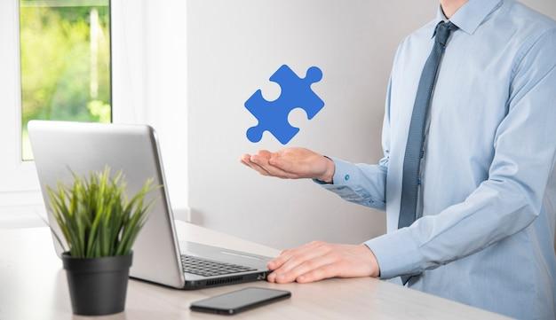 ビジネスマンは彼の手にパズルジグソーパズルのピースを持っています。ビジネスにおける協力、チームワーク、ヘルプとサポートの概念。