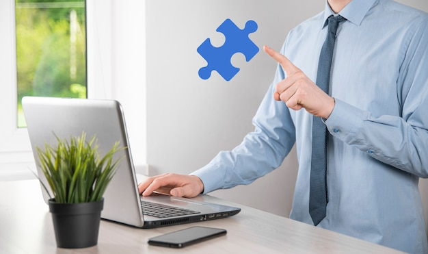 사업가는 손에 퍼즐 조각을 들고 있습니다. 협력, 팀워크, 도움 및 비즈니스 지원의 개념입니다.