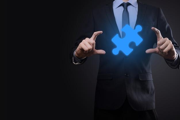 ビジネスマンは彼の手でパズルジグソーパズルのピースを持っています。協力の概念