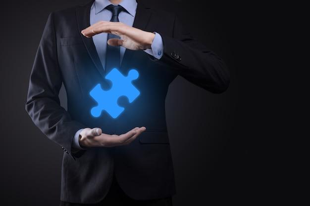 사업가 그의 손에 퍼즐 퍼즐 조각을 보유합니다. 협력의 개념