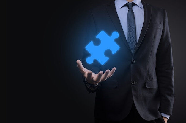 사업가 그의 손에 퍼즐 퍼즐 조각을 보유