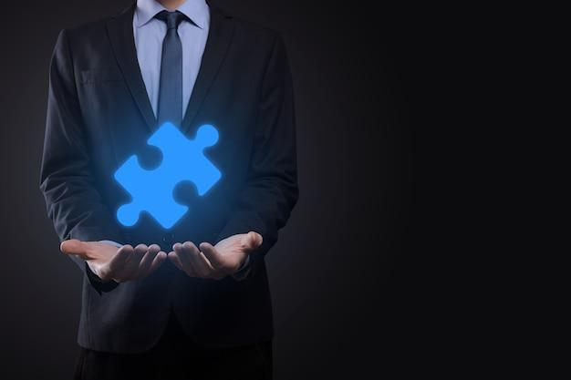 ビジネスマンは彼の手でパズルジグソーパズルのピースを持っています