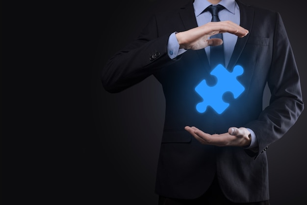 사업가 그의 손에 퍼즐 퍼즐 조각을 보유하고있다.