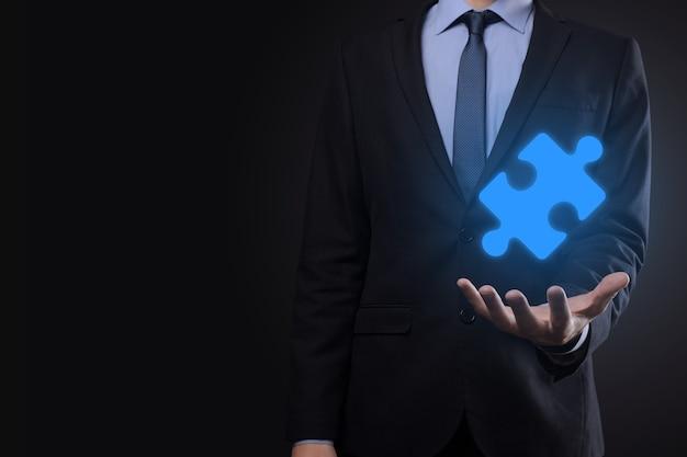 Бизнесмен держит в руках кусок головоломки