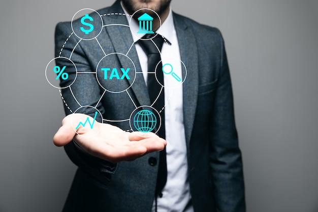 ビジネスマンは彼の手に税のアイコンを持っています