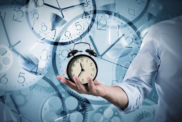 사업가는 여러 번 표시하는 시계에 그의 손에 알람 시계를 보유