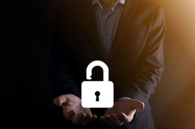 Бизнесмен держит значок открытого замка на ладони. разблокировка виртуального замка. бизнес-концепция и технологическая метафора для кибератак, компьютерных преступлений, информационной безопасности и шифрования данных. Premium Фотографии