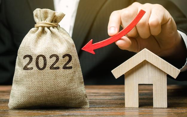 A businessman holds an arrow down near the house and a 2022 money bag