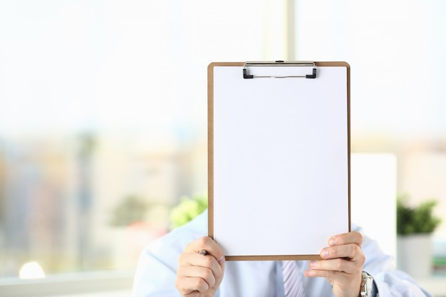 Businessman holds clipboard with paper