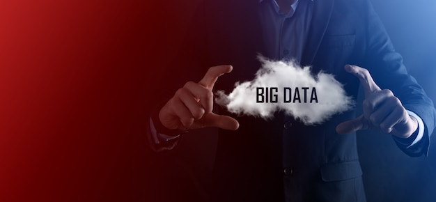 Businessman holds cloud with inscription, word big data. icon. on dark background.