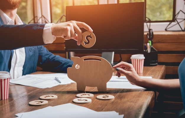 Businessman holds a coin near wooden piggy.
