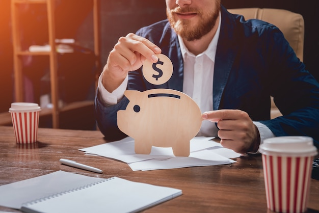 Businessman holds a coin under wooden piggy.