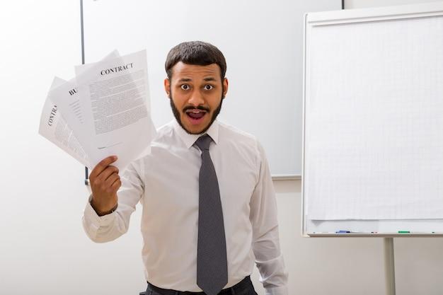 사업가는 계약서가 있는 손 사무원에 계약서를 보유하고 있습니다.