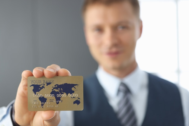 Businessman holds a credit bank card closeup