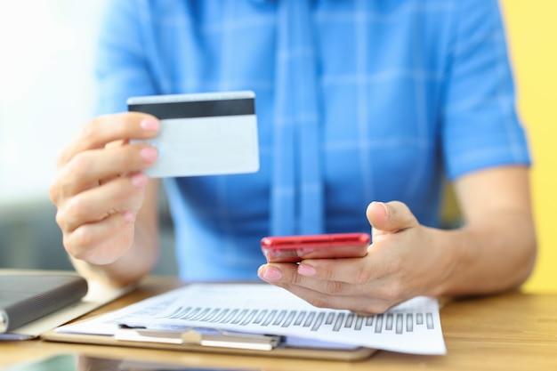 ビジネスマンは、モバイルアプリを介してクレジット銀行のプラスチックカードとスマートフォンのオンライン支払いを保持しています